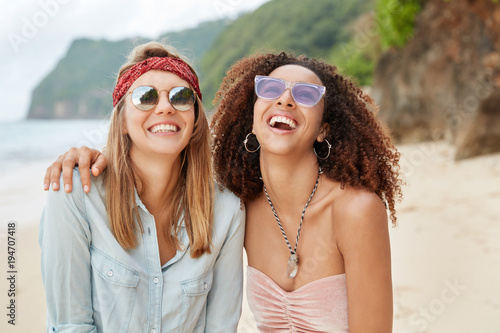 Fotografía  Happy female gay couple of different nationalities, embrace each other, laugh joyfully and pose at camera against cliff and seascape