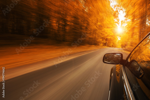 Photo sur Toile Rouge mauve Close up of a car speeding on the empty, autum road with copy space
