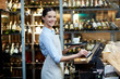 canvas print picture - Young cheerful waitress registrating an order and carrying it to the client