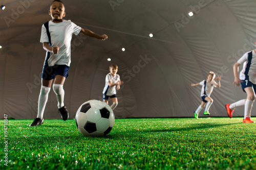 Tuinposter Voetbal Soccer ball on green pitch and little players running towards it during game