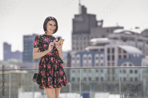 Foto Smart beautiful caucasian fit business woman with a strong face type and dark bob short hairstyle in casual romantic dress in european city streets with phone in hands, working, smiling