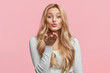 Pretty blonde woman blows passionate kiss into camera, expresses her love, isolated over pink background. Adorable young female model makes air kiss. People, body language and beauty concept