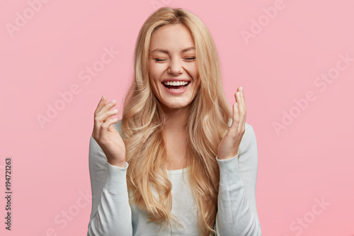 Isolated shot of joyful blonde young cute woman laughs joyfully as hears funny anecdote from friend, has long light hair, poses against pink studio wall Fototapet