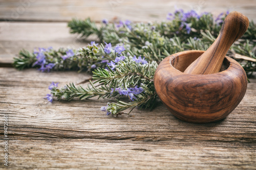 Fresh blooming rosemary and a mortar on a wooden table, copy space Fototapeta