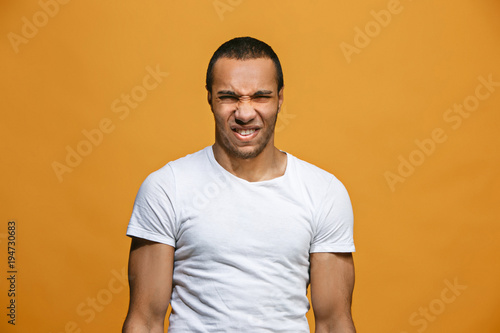 Fotografie, Tablou  Young man with disgusted expression repulsing something, isolated on the orange