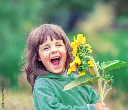 Photo  Happy laughing little girl with sunflower outdoors in summer