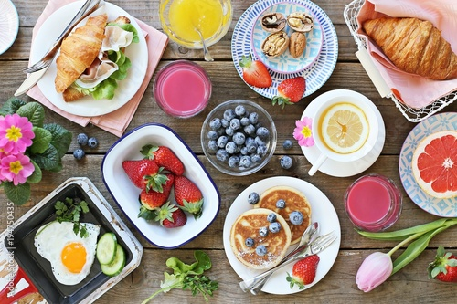 Fototapeta Breakfast food table. Festive brunch set, meal variety with fried egg, pancakes, croissants, smoothie ,fresh berries and fruits. Overhead view obraz