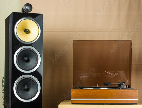 Vintage turntable playing a vinyl record and modern black speakers Wallpaper Mural