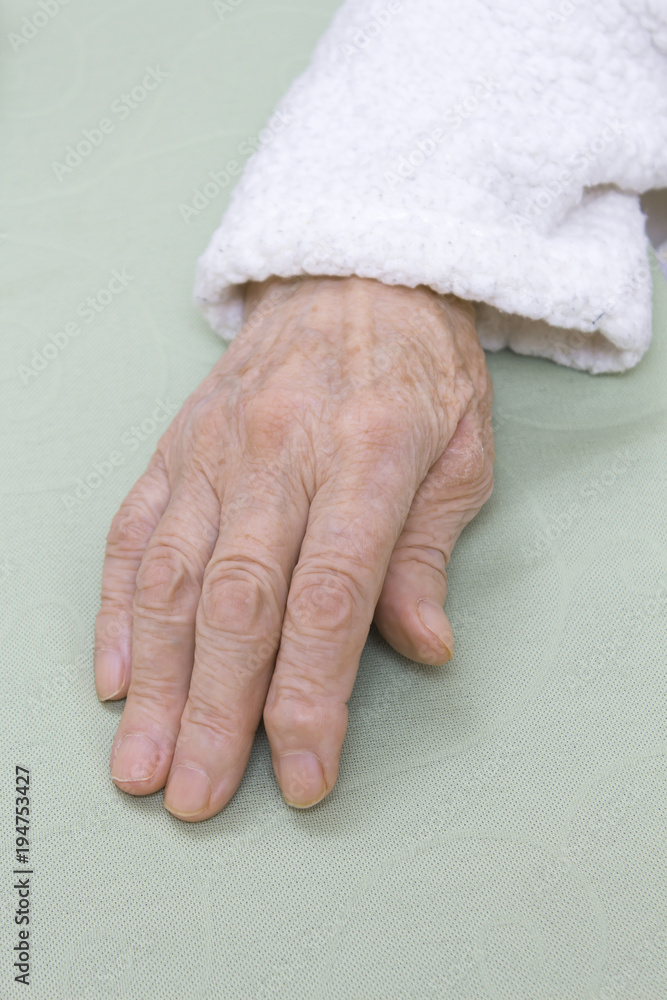 Fototapeta Stara zniszczona skóra dłoni bardzo starej kobiety w białym szlafroku na jasnym tle.