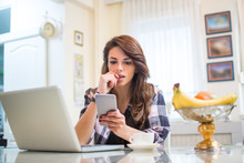 Young Nervous Woman Looking At Smartphone And Biting Her Fingernails At Home.