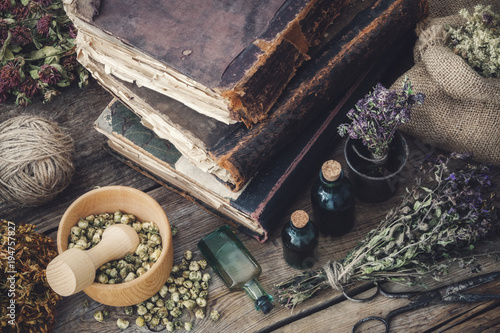 Fotografie, Obraz  Tincture bottles, assortment of dry healthy herbs, old books, mortar, scissors on old wooden desk