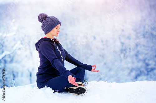 Beautiful woman meditating in winter park