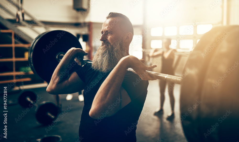 Fototapety, obrazy: Mature man working out with weights in a gym