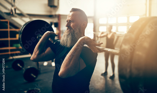 Mature man working out with weights in a gym Wallpaper Mural
