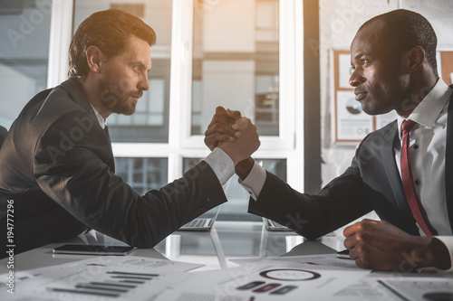 Fototapety, obrazy: Challenge. Side view profile of two strong attractive entrepreneurs in formal clothes are sitting at desk in modern office and arm wrestling. They are looking at each other intently
