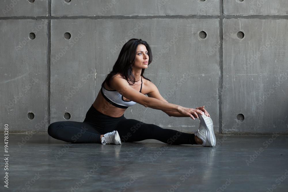 Fotografia athletic brunette woman stretching legs