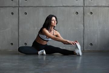 lekkoatletycznego brunetka kobieta rozciąganie nogi