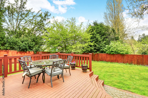Photo Large deck with dining space overlooking spacious back yard.