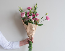 Woman's Hand Holding Bouquet Of Pink Lisianthus Flowers Wrapped In In Brown Paper Against Neutral Wall Background