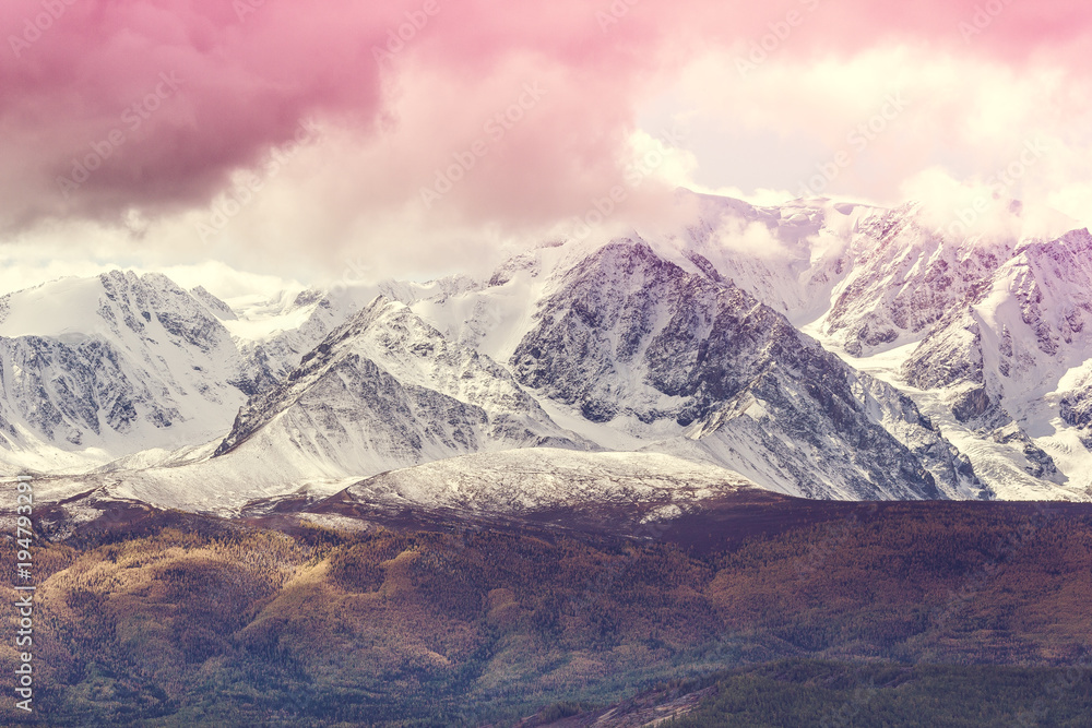 The peaks of the snowy mountain range under the pink sky. Landscape rocks in pastel color.