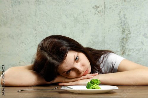 Valokuva  sad young brunette woman dealing with anorexia nervosa or bulimia having small green vegetable on plate