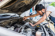 Fixing car engine in automobile repair garage. Handsome mechanics in uniform are repairing car while working in auto service