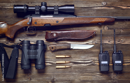 Autocollant pour porte Chasse Hunting rifle and ammunition on a wooden background.