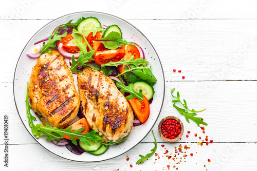 Fotobehang Kip Grilled chicken breast. Fried chicken fillet and fresh vegetable salad of tomatoes, cucumbers and arugula leaves. Chicken meat salad. Healthy food. Flat lay. Top view. White background