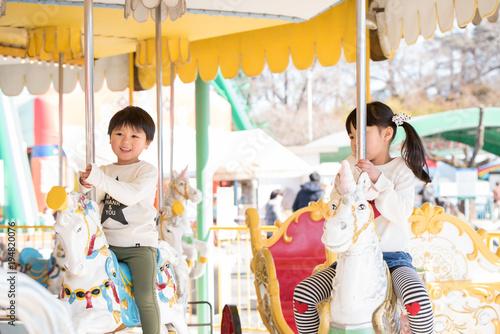 Fotobehang Amusementspark メリーゴーランドに乗る子供