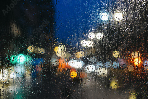 Fotobehang Londen rode bus Emotional melancholic abstract background with defocused lights bokeh in London, UK behind rain drops in window glass, Focus on few drops due to the shallow depth of field