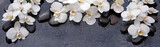 Spa background with white orchid and black stones.