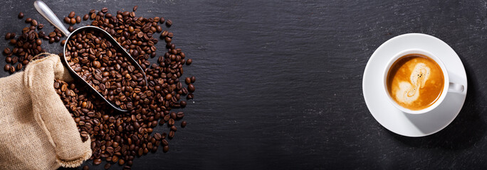 cup of coffee and coffee beans in a sack, top view