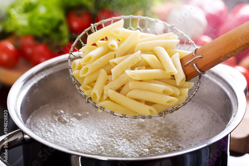 Fotografering  Cooking pasta in a pot with boiling water