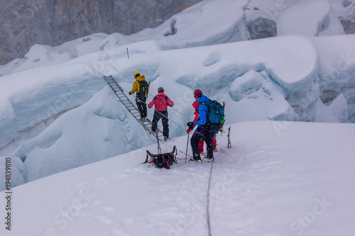 Fotografía Climbers crossing a crevasse over a ladder, Island Peak, Everest Region, Nepal