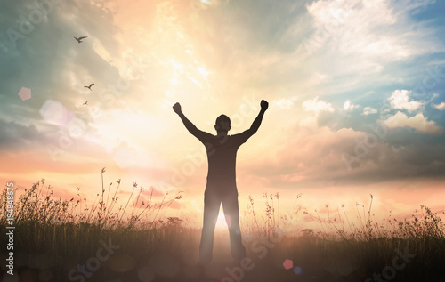 International human rights day concept: Silhouette of man raised hands at sunset Fototapete