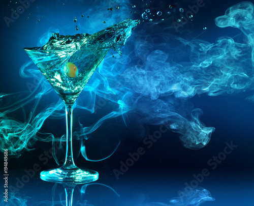 martini cocktail splashing in dark blue smoky background