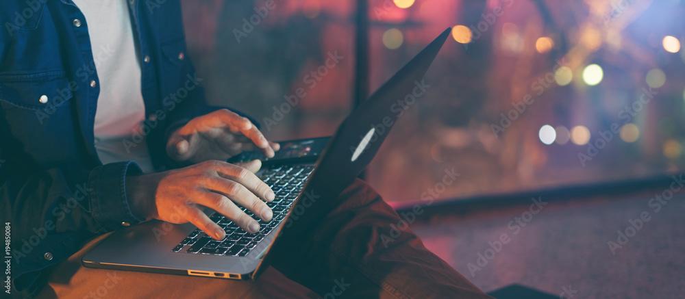 Fototapeta Man working on laptop at night