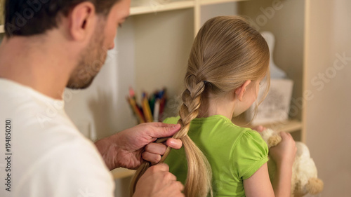 Fotografía  Responsible good father braiding little daughters hair, preparations for school