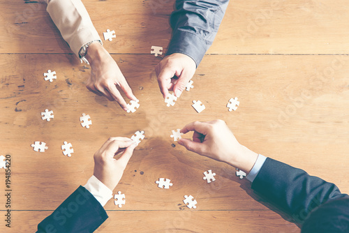 Businessman Team Work Holding Two Jigsaw Connecting Couple