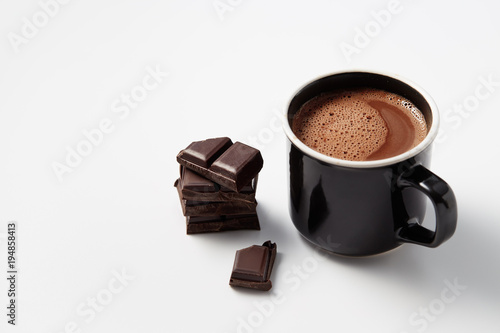 Staande foto Chocolade Black mug with hot chocolate served with chunks of dark chocolate