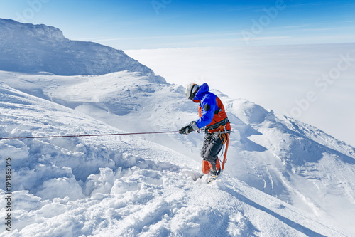 Foto op Plexiglas Alpinisme Equipped climber ascent by snowy slope with climbing rope on the top of peak in snowy alpine mountains. Life guard professional man on the work in high mountains. Action in hard conditions scene.