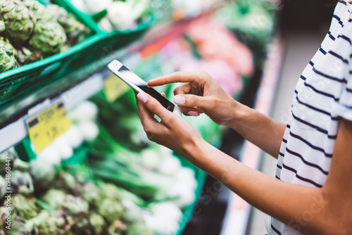 woman shopping purchase healthy food in supermarket blur background, view girl blogger buy products using smartphone in store. Hipster at grocery using smartphone. Person comparing price