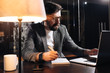 Bearded project manager hold pen in hand and using contemporary notebook. Young businessman working in loft office at night. Man making new startup