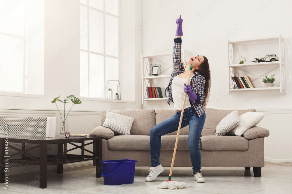 Fototapeta Happy woman cleaning home with mop and having fun