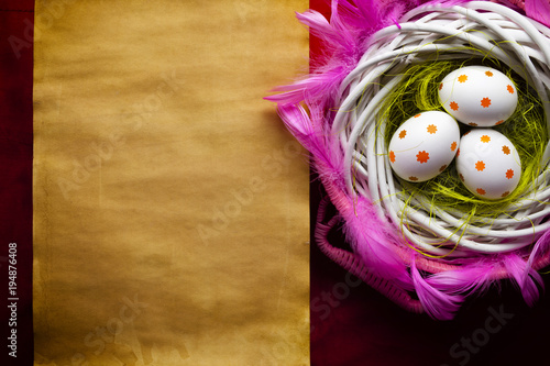 Three white Easter eggs in the nest and blank handmade paper sheet Canvas Print