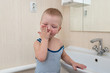A cute little blond boy washes his hands before eating in the bathroom. The concept of cleanliness and hygiene.