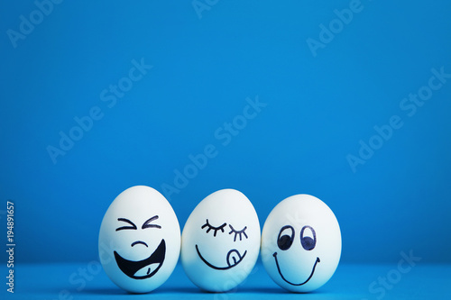 Eggs with funny faces on blue background