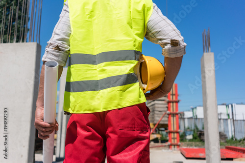 Midsection rear view of a worker holding a rolled blueprint and a midsection rear view of a worker holding a rolled blueprint and a yellow hard hat while malvernweather Image collections