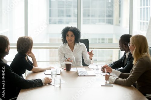 Black female boss leading corporate multiracial team meeting talking to diverse Fototapet