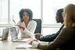 Leinwandbild Motiv African businesswoman showing good statistics report explaining deal advantages convincing multiracial partners at negotiations meeting, black manager consulting diverse clients promising benefits